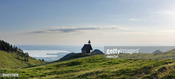 Panoramic view of Steinling Alm Chapel below Kampenwand mountain with Lake Chiemsee in the distance, Chiemgau, Upper Bavaria, Germany