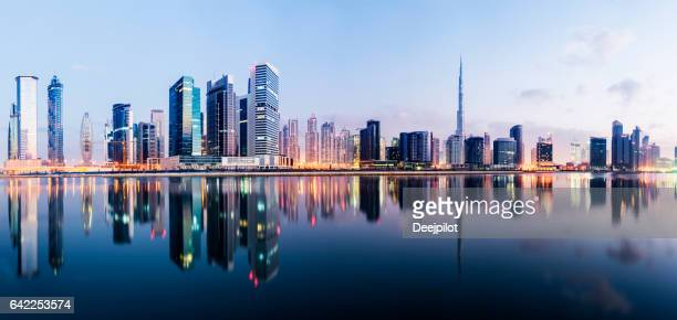 Panoramic view of the Dubai downtown and business park district at twilight with reflection in the still lake water, United Arab Emirates