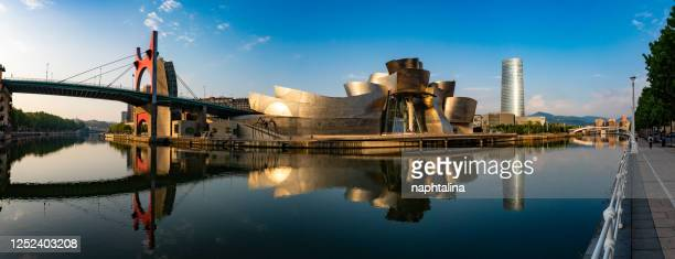 panoramic view of the guggenheim museum bilbao reflected in the bilbao river at dawn - bilbao stock pictures, royalty-free photos & images