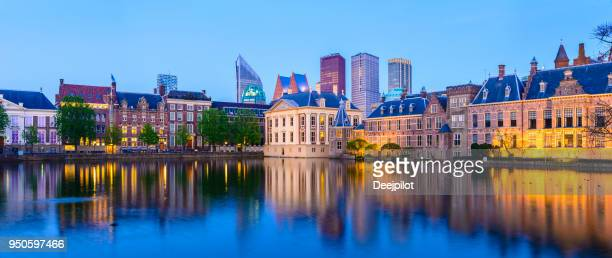 panoramic view of the hague downtown city skyline and parliament buildings at twilight, netherlands - binnenhof stock photos and pictures