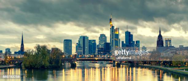 Panoramic view of the illuminated Frankfurt am Main skyline with Alte Brucke and the Dom with moody sky at dusk