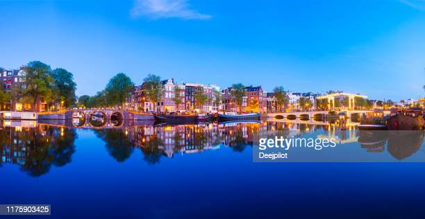 panoramic view of the magere brug bridge and canal side houses on the amstel river at twilight, amsterdam, netherlands - amsterdam stock pictures, royalty-free photos & images
