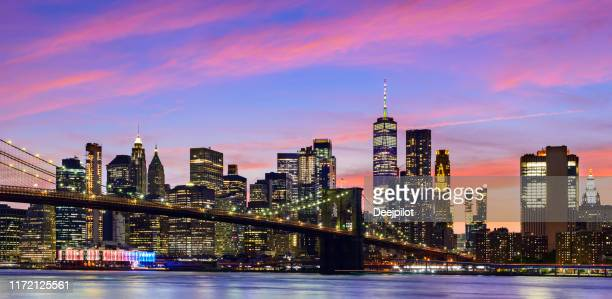 panoramic view of the manhattan city skyline and brooklyn bridge at twilight, new york, usa - new york city stock pictures, royalty-free photos & images