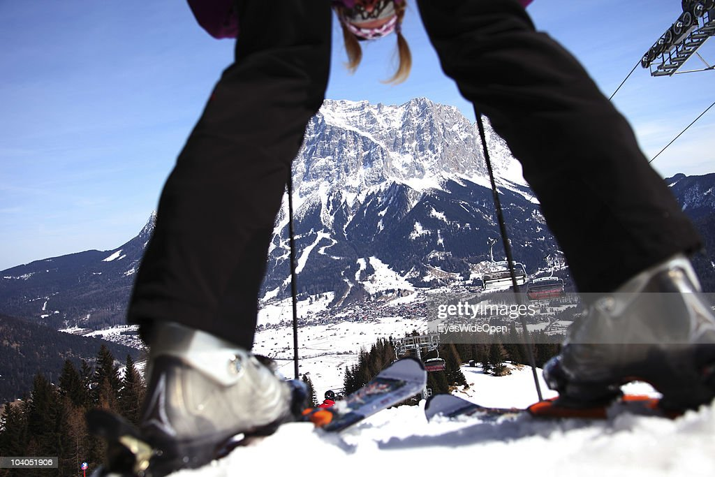 Panoramic view of the mountain Zugspitze seen through the legs of a female skier on March 19, 2010 in Lermoos, Tyrol, Austria. The Zugspitze has got an altitude of 2962 meters and is the highest mountain and only glacier of Germany.