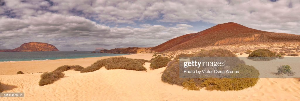 Panoramic view of the sand dunes and the desert like landscape at Las Conchas beach with Volcano Montaña Bermeja (the Red Mountain) in the background in Lanzarote, Canary Islands, Spain : Foto de stock