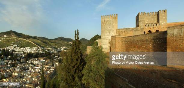 Panoramic view of the towers of the Alcazaba and at sunset with the Sacromonte and the Albaicin neighbourhoods in the background in Granada, Andalusia, Spain