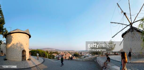 panoramic view of tourists taking pictures in front of old windmills at sunset at alacati. - emreturanphoto stock pictures, royalty-free photos & images
