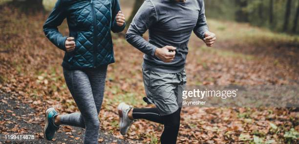 panoramic view of unrecognizable athletic couple jogging during autumn day in nature. - warming up stock pictures, royalty-free photos & images