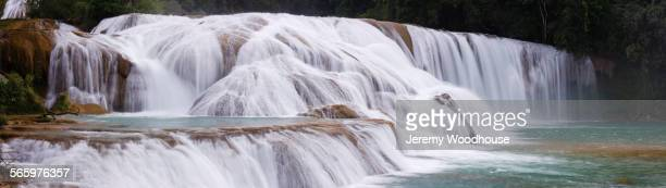 Panoramic view of waterfall pouring over rocks in river