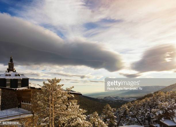 Panoramic view of winter rural scene on sunny day with dramatic sky.