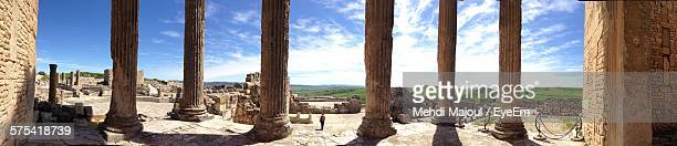 panoramic view of woman standing amidst large columns at dougga against sky - túnez áfrica del norte fotografías e imágenes de stock