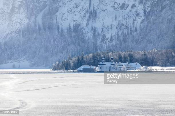 panoramic view on frozen lake koenigssee with mountain range in the background; chapel st. bartholomew - koenigssee, bavaria, germany - königssee bavaria stock photos and pictures