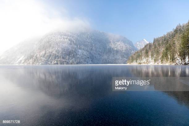 panoramic view on frozen lake koenigssee with mountain range in the background - koenigssee, bavaria, germany - königssee bavaria stock photos and pictures