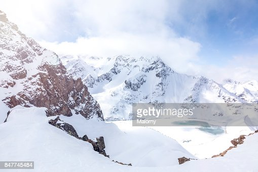 Panoramic view on snow-capped mountains and frozen lake