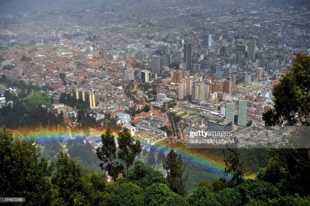 Panoramic view taken from the Cerro de Monserrate of a rainbow with city of Bogota in the background, in Colombia, on July 27, 2013. AFP PHOTO/Guillermo LEGARIA /