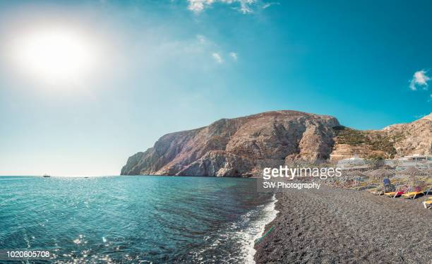 panoramic view the black sand beach in santorini, greece - riva dell'acqua foto e immagini stock