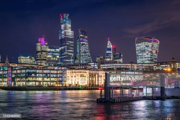 panoramic view towards city of london financial and business district during crear night with evening illumination - creative stock image - london skyline stock pictures, royalty-free photos & images