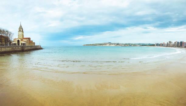 Panoramic views of an urban beach, San Lorenzo beach and San Pedro church in Gijón