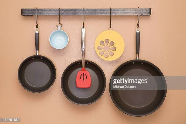 Pans and Utensils Hanging on Kitchen Wall