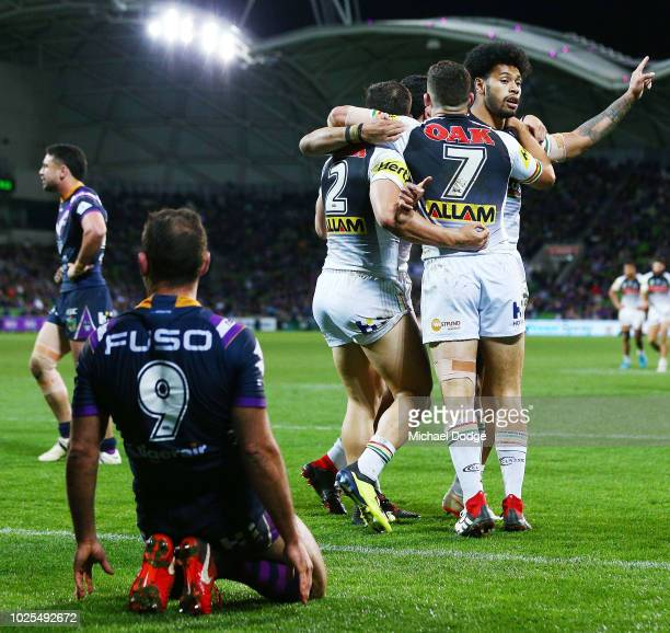 Panthers players celebrate after Josh Mansour of the Panthers scores a try past Cameron Smith of the Storm during the round 25 NRL match between the...