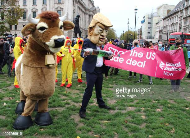 Pantomime cow and a flock of chlorinated chickens try to avoid being injected with hormones by a fake Donald Trump and a businessman during the...