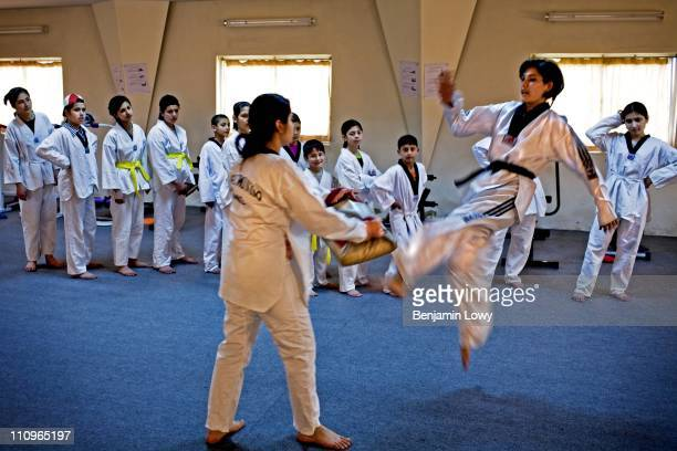 Pants wearing Afghan Tae Kwon Do instructor demonstrates a flying kick to a mixed class of young girls and boys in a women and children's only gym on...