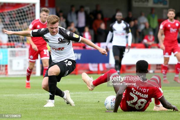 Panutche Camara of Crawley Town slides in to tackle Mark Shelton of Salford City during the Sky Bet League Two match between Crawley Town and Salford...