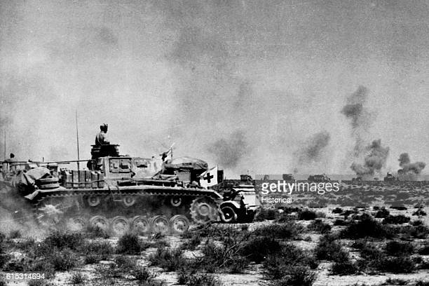 A Panzer rolls past a medical aid station displaying a red cross flag