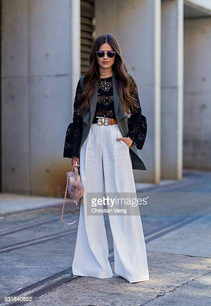 Paola Alberdi wearing a black sheer top with long sleeves a nude Chanel bag and white wide leg pants outside By Johnny at MercedesBenz Fashion Week...