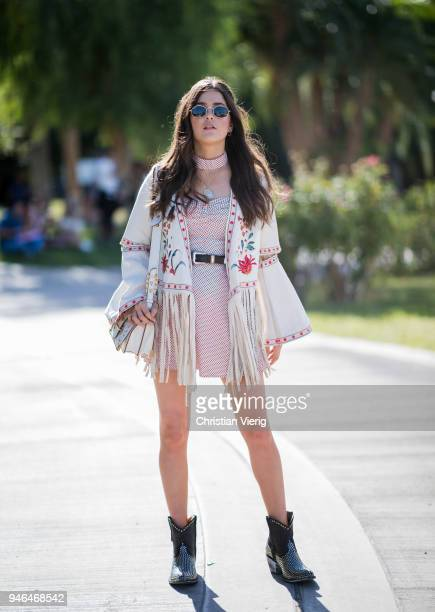 Paola Alberdi wearing jacket with fringes, bag, dress, boots is seen at Revolve Festival on April 14, 2018 in Indio, California.