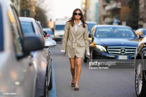 Paola Alberdi wears sunglasses a bag with a golden chain strap a beige oversized blazer jacket/dress a white shirt a necklace outside Bottega Veneta...