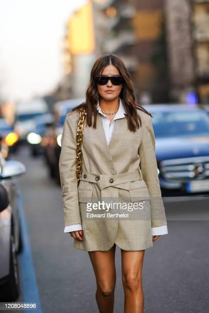 Paola Alberdi wears sunglasses, a bag with a golden chain strap, a beige oversized blazer jacket/dress, a white shirt, a necklace, outside Bottega...