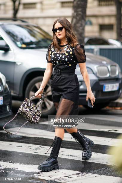 Paola Alberdi wears sunglasses, a black lace mesh dress with colored floral embroidery, a belt, black leather boots, earrings, a bag, outside Miu...