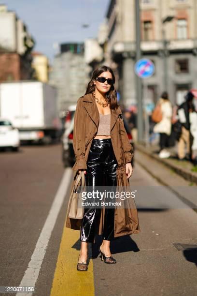 Paola Alberdi wears sunglasse,s a chain necklace, a brown long coat, a gray crop top, black shiny pants, a brown bag, mesh shoes, outside Max Mara,...