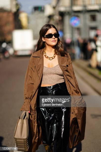 Paola Alberdi wears sunglasse,s a chain necklace, a brown long coat, a gray crop top, black shiny pants, a brown bag, outside Max Mara, during Milan...