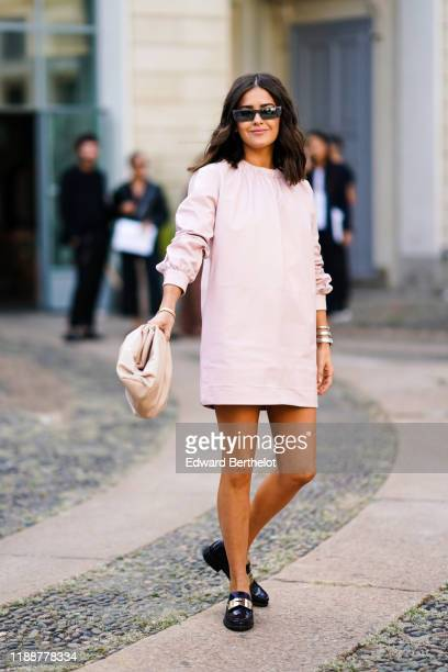 Paola Alberdi wears sunglasses, a light pink leather long sleeves mini dress, a beige puff clutch, black moccasins with a metallic strap, outside the...