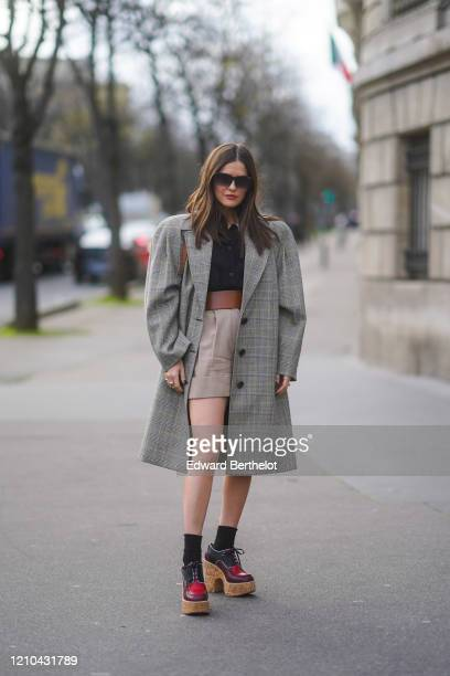 Paola Alberdi wears sunglasses, a long gray checked pattern oversized blazer jacket with shoulder pads, a brown leather large belt, a navy blue...