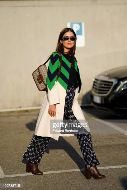Paola Alberdi wears sunglasses a long Gucci coat with green and black stripes Gucci monogram flared navy blue pants brown leather pointy shoes a...