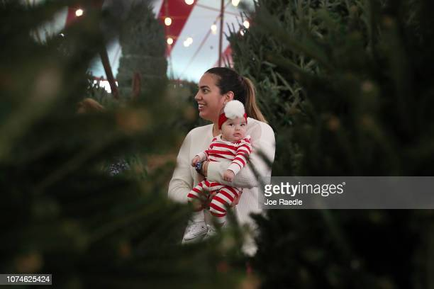 Paola Gonzalez holds her daughter Penelope Gonzalez 3 months old as she shops for a Christmas tree at a Holiday Sale Christmas Tree lot on November...