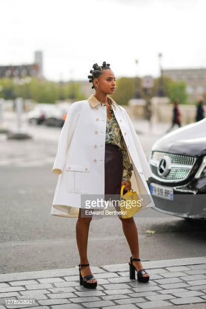 Paola Locatelli wears a white coat, a floral print pale green shirt, a brown leather skirt, a yellow bag, black shoes, outside Louis Vuitton, during...