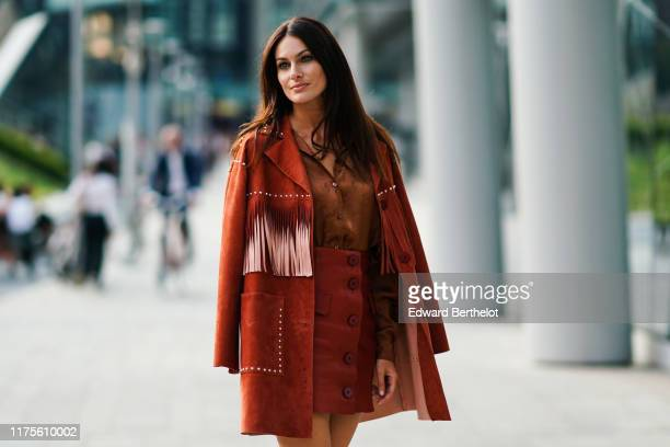 Paola Turani wears a brown suede jacket with fringes a brown silky lustrous shirt a leather skirt outside the Alberta Ferretti show during Milan...