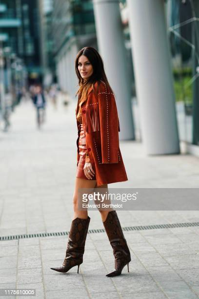 Paola Turani wears a brown suede jacket with fringes a brown silky lustrous shirt a leather skirt leather high boots outside the Alberta Ferretti...