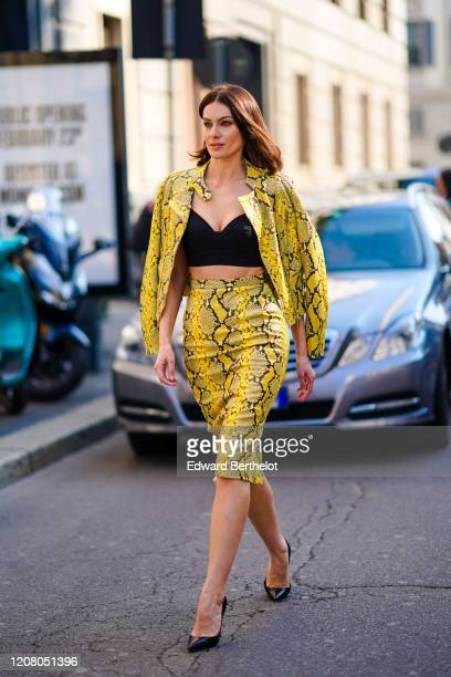 Paola Turani wears black bras yellow snake pattern printed jacket a leather skirt pointy shoes outside Ermanno Scervino during Milan Fashion Week...