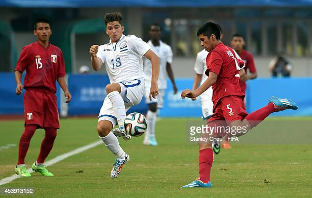 Paolo Belloni of Honduras Challenges Carlos Huerto of Peru during the 2014 FIFA Boys Summer Youth Olympic Football Tournament Preliminary Round Group...