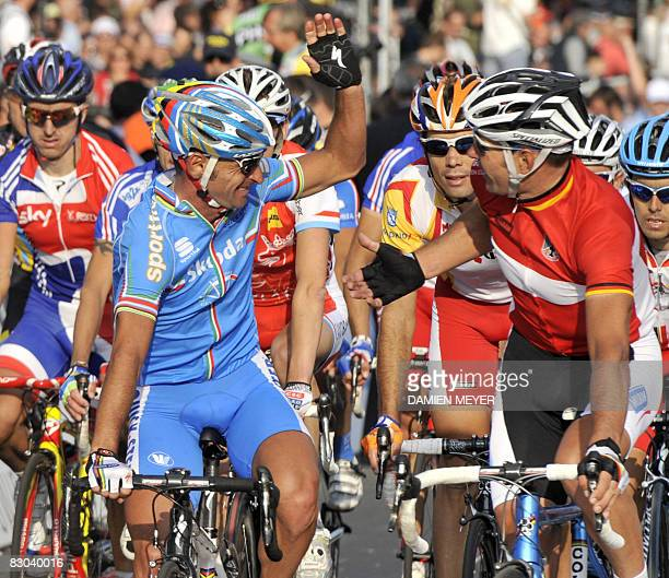 Paolo Bettini of Italy and German Erik Zabel give eachother a high five as Spaniard Oscar Freire looks on at the end of the elite men road race at...