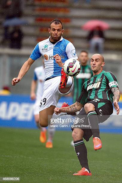 Paolo Cannavaro of US Sassuolo Calcio competes the ball with Riccardo Meggiorini of AC Chievo Verona during the Serie A match between US Sassuolo...
