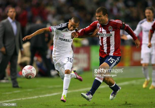 Paolo Cardozo of the Los Angeles Galaxy vies for position to the ball with Alejandro Moreno of Chivas USA in the first half during the MLS match at...