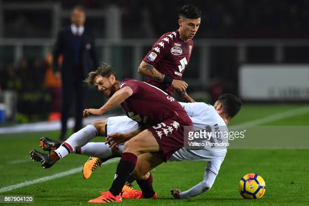 Paolo Farago of Cagliari Calcio is tackled by Cristian Ansaldi and Daniele Baselli of Torino FC during the Serie A match between Torino FC and...