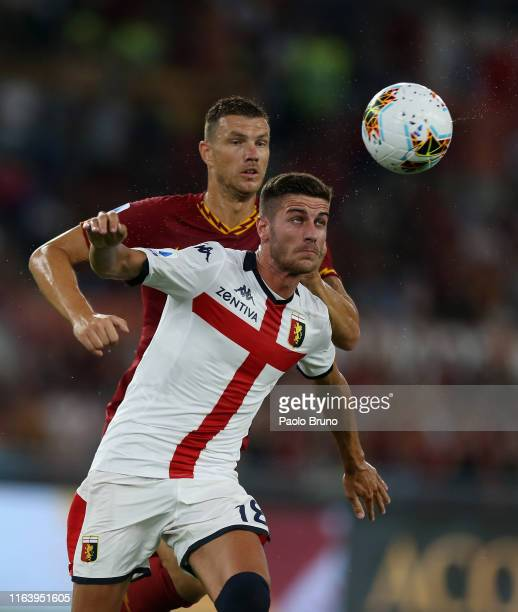 Paolo Ghiglione of Genoa CFC competes for the ball with Edin Dzeko of AS Roma during the Serie A match between AS Roma and Genoa CFC at Stadio...
