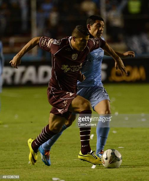 Paolo Goltz of Lanús struggles for the ball with Walter Flores of Bolívar during a second leg quarter final match between Bol'ívar and Lanúœs as part...